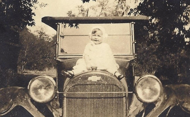 old family photo of baby on car